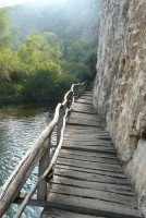Wooden bridge by the cliff over the river